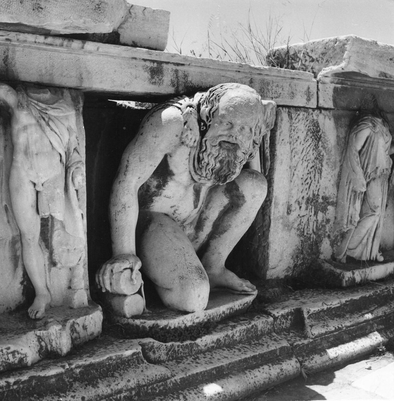 Dionyssos, among other sculpture at the hyposcenium  (the low wall supporting the front of the stage in a Greek theater) of the Theater of Dionyssos. Photo by N. Tombazi.